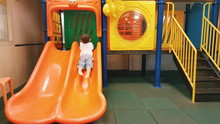 Rear View Of Boy Playing On Jungle Gym In Room