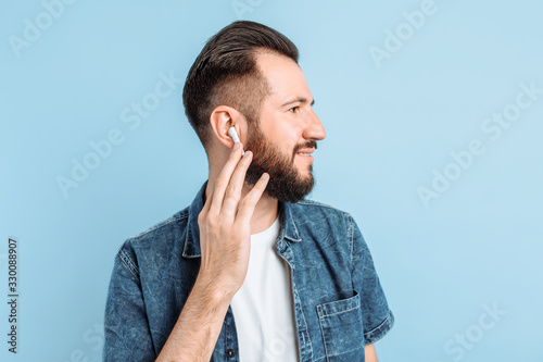 A man in wireless headphones on a blue background Canvas-taulu