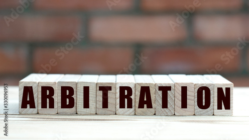 Photo concept word arbitration on cubes against the background of a brick wall