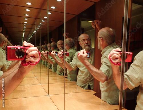 Obraz Multiple Reflection Of Senior Man Taking Selfie Through Camera In Restroom - fototapety do salonu