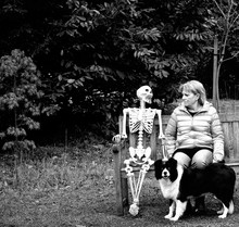 Woman Sitting By Human Skeleton On Bench At Park