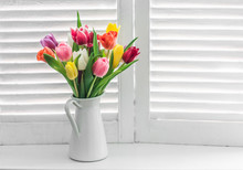 Bouquet With Multicolored Tulips On A Window With Wooden Shutters On A Light Background