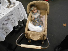 High Angle View Of Doll In Wicker Baby Carriage