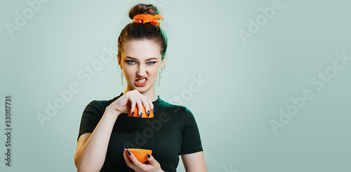 Photo teenager girl grimacing with halves an orange on a studio green background, impu