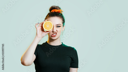 teenager girl grimacing with half an orange on a studio green background, impude Canvas Print