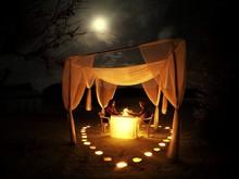 Couple Having Candlelight Dinner In Gazebo At Night