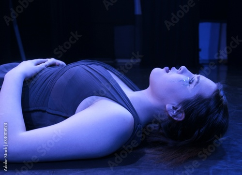 Leinwand Poster Side View Of Dancer Lying On Stage