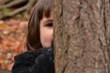 Portrait Of Little Girl Hiding...