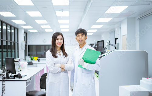 two young smiling scientist in white lab coat standing with automation blood ana Canvas Print