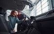Professional salesman assisting young girl by choosing new modern automobile indoors. Woman sitting inside
