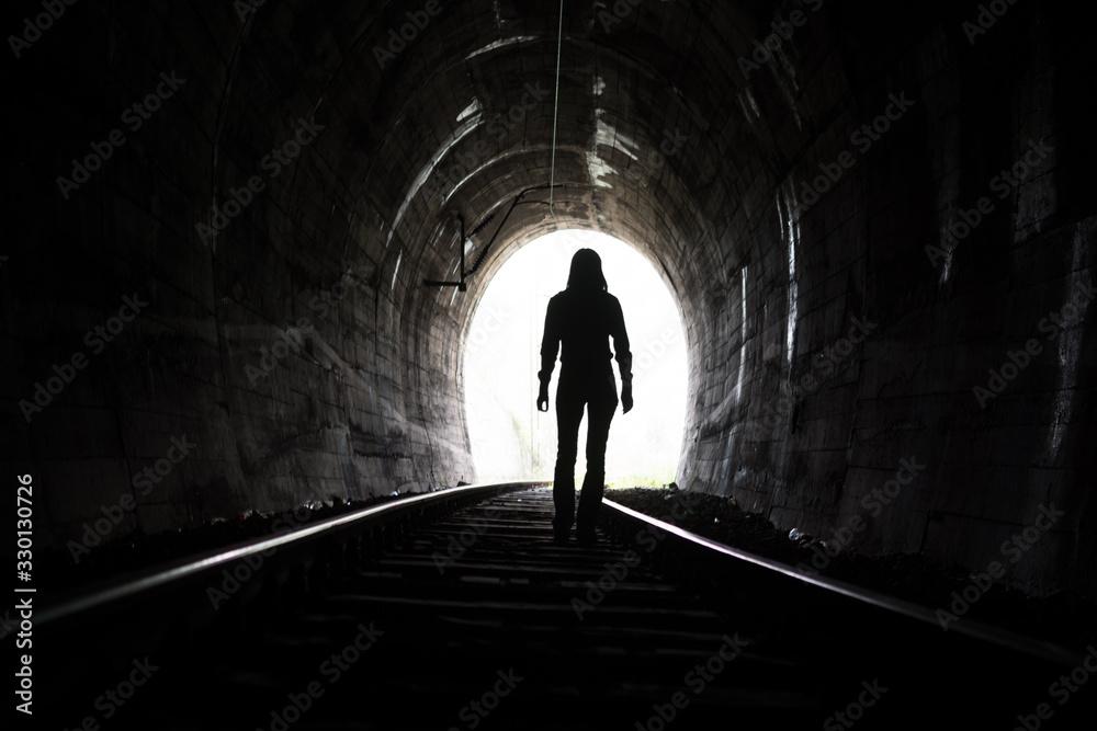 Fototapeta Rear View Of Woman Standing On Railroad Track In Tunnel