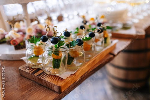 Glasses with seafood snacks and meat on banquet table Wallpaper Mural