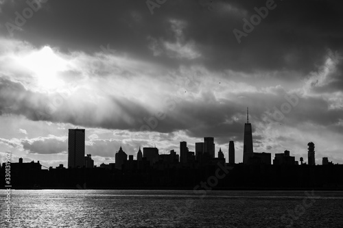 Black and White Lower Manhattan Skyline on the East River in New York City during Sunset with Skyscraper Silhouettes