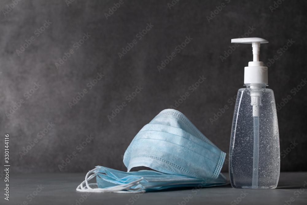 Fototapeta Sanitizer gel or antibacterial soap and face mask for coronavirus preventive measure