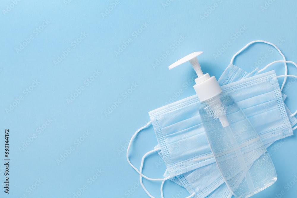Fototapeta Sanitizer gel or antibacterial soap and face mask for coronavirus preventive measure, top view