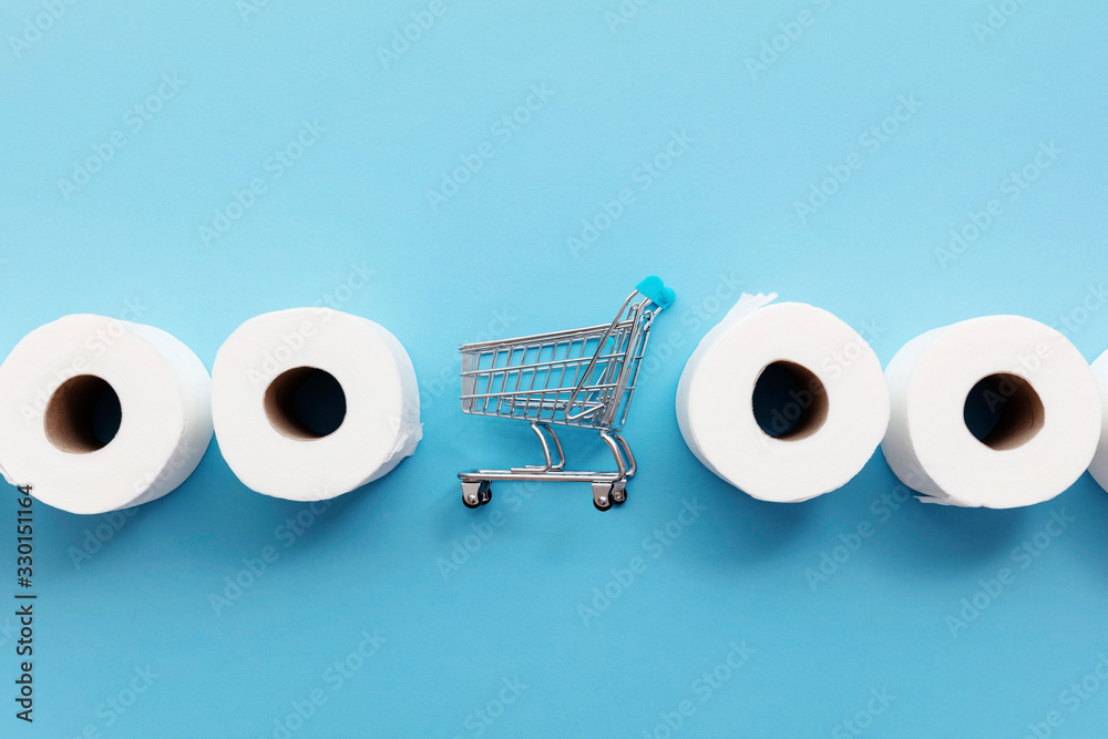 Fototapeta Roll of white toilet paper with a shopping cart on a blue background