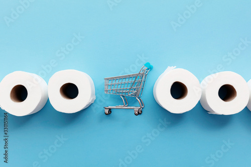 Obraz Roll of white toilet paper with a shopping cart on a blue background - fototapety do salonu