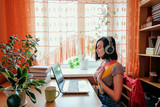 Fototapeta Zwierzęta - Female in headphones sits at front of laptop and breathing. Online audio meditation concept.