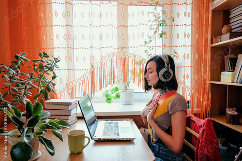 Obraz Female in headphones sits at front of laptop and breathing. Online audio meditation concept. - fototapety do salonu