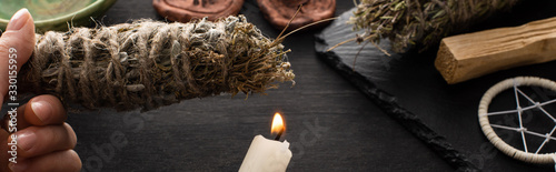 Cropped view of shaman holding smudge stick and candle near witchcraft on black Wallpaper Mural