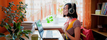 Female In Headphones Sits At Front Of Laptop And Breathing. Online Audio Meditation Concept.