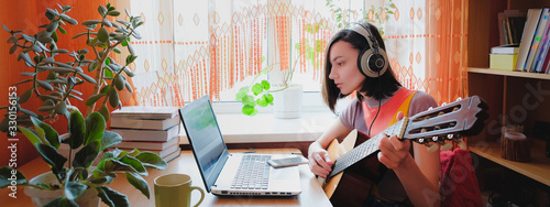 Female self education online. Woman plays guitar at front of laptop