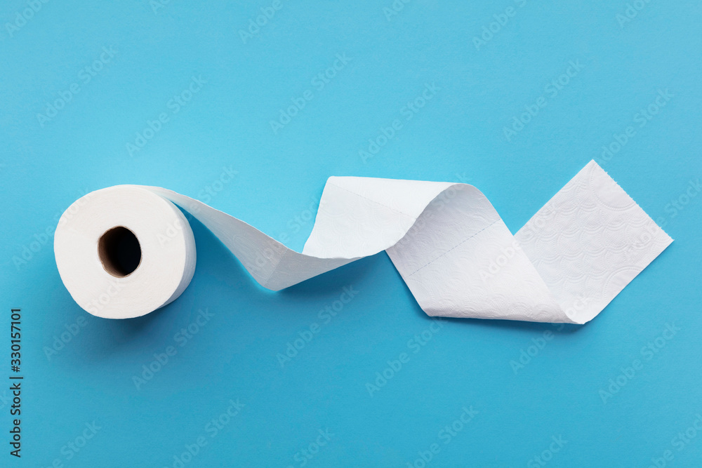Fototapeta A single roll of toilet paper unrolled on a blue background