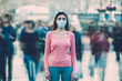 The young female with medical mask on her face stands on the crowded street