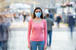 The young girl with medical mask on her face stands on the crowded street