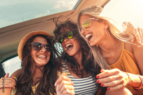 Three female friends enjoying traveling in the car. Sitting in rear seat and having fun on a road trip.