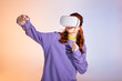 emotional teen girl gesturing and using virtual reality headset, on purple and beige