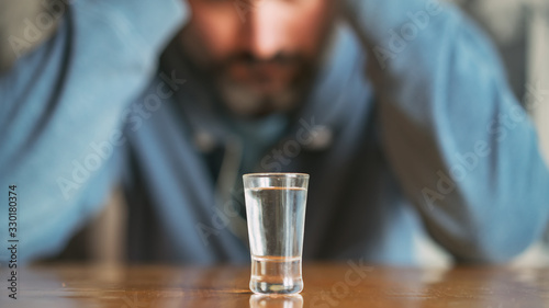 Photo alcoholic sits at kitchen table with glass of vodka at home