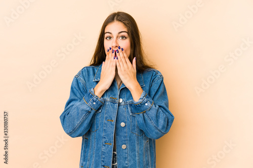 Young caucasian woman isolated en beige background shocked, covering mouth with hands, anxious to discover something new Wallpaper Mural