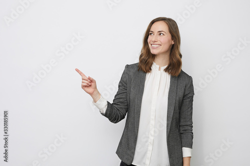 Fototapeta Beautiful businesswoman is looking happy and pointing at your product obraz