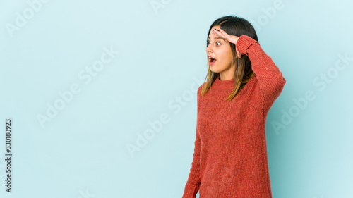 Young woman isolated on blue background looking far away keeping hand on forehead.