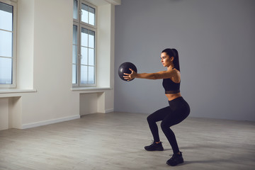 The girl goes in for sports with a medical ball. A sports girl does exercises in a room indoors.