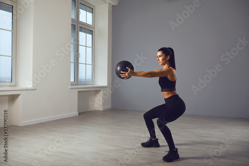 obraz PCV The girl goes in for sports with a medical ball. A sports girl does exercises in a room indoors.