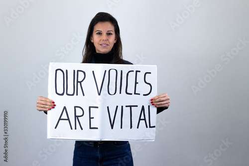 Fototapeta attractive  middle age woman activist hold up protesting sign saying Our voices are vital isolated on gray background studio shot, dark air