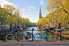 Bicycles Lining A Bridge Over The Canals Of Amsterdam With Church In Background. Late Day Light. Netherlands.