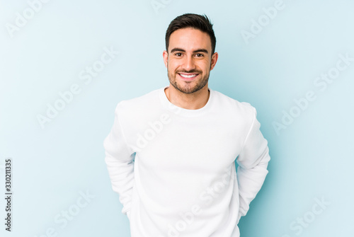 Obraz Young caucasian man isolated on blue background happy, smiling and cheerful. - fototapety do salonu