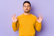 Young caucasian man isolated on purple background relaxes after hard working day, she is performing yoga.