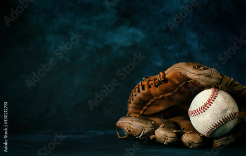 Obraz Baseball glove with ball close up in studio with dark texture backdrop, copy space for sport graphic concept. - fototapety do salonu