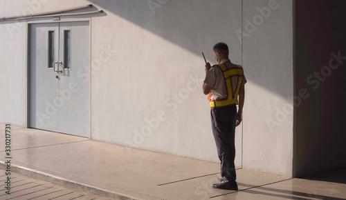Fotografie, Obraz Asian security guard in safety vest walking on sidewalk and using walkie talkie