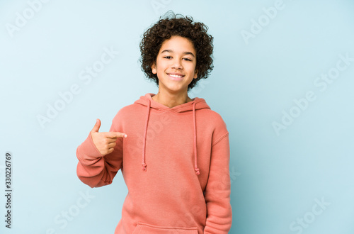 Obraz African american little boy isolated person pointing by hand to a shirt copy space, proud and confident - fototapety do salonu