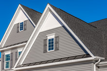 Double Gable, With White Decorative Trim Over The Windows On A Triangle Gable Roof, White Soffit And Fascia,  Gray Horizontal Vinyl Lap Siding With Blue Sky Background