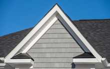 Plastic Or Wood White Roof Decoration Gable, Corbel, Louver On A New Construction Luxury American Single Family Home In The East Coast USA With Blue Sky Background, Gray Shingles Shakes White Accent