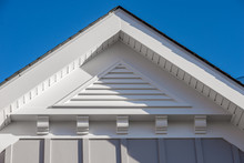 Close-up View Of A White PVC Triangle Gable Vent Above A Decorative Trim Board On A Newly Built American Single Family Home