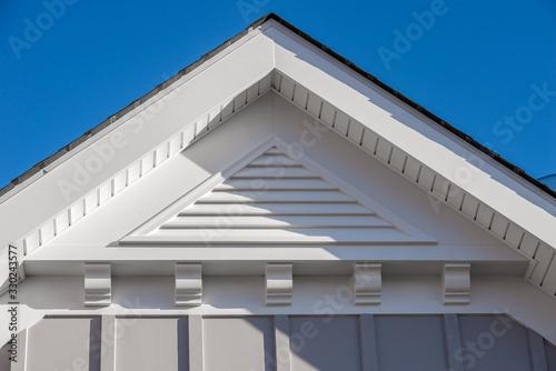 Photo Close-up view of a white PVC triangle gable vent above a decorative trim board o
