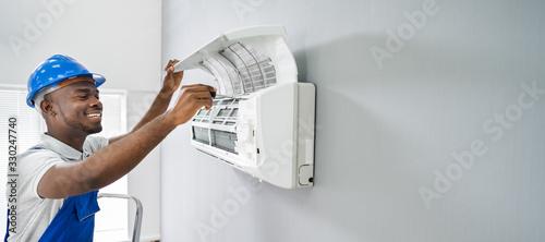 fototapeta na ścianę Technician Repairing Air Conditioner