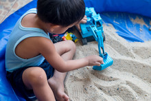 Toy Truck And Boy  Playing In The Sandbox